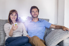 Couple watching a movie with a video projector, on comfortable sofa. Cheerful men and women sitting on a couch looking at a film in home cinema stock photo