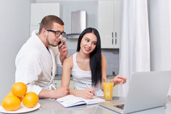 Couple watching news at laptop in morning. Morning of couple at kitchen, where brunette women using lap top and writing her plan of day. Husband in robe talking Stock Photos