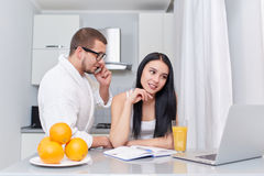 Couple watching news at laptop in morning. Morning of couple at kitchen, where brunette women using lap top and writing her plan of day. Husband in robe talking Royalty Free Stock Image