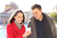 Couple watching phone content in winter in the street. Couple watching smart phone content in winter in a coast town street stock photography