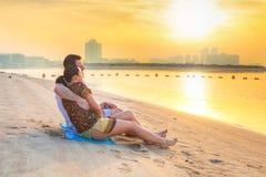 Couple watching romantic sunrise on the beach stock photo