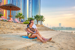 Couple watching romantic sunrise on the beach. Of Abu Dhabi Royalty Free Stock Photo