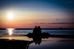 Couple watching a romantic sunset Stock Photos
