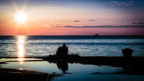 Couple watching a romantic sunset Stock Photography