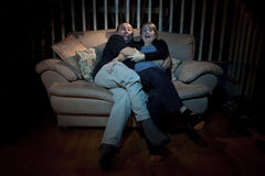Couple watching scary movie on TV. Couple on couch watching scary movie on TV Stock Images