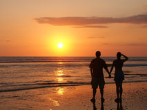 Couple watching the setting sun hand in hand royalty free stock photo