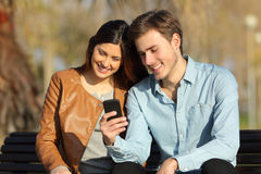 Couple watching a smart phone sitting on a bench Stock Photo