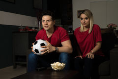Couple watching a soccer game in the dark Stock Photography