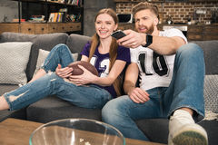 Couple watching sports game at home Royalty Free Stock Photography