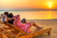 Couple watching sunrise on the beach of Red Sea stock photo