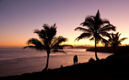Couple watching sunrise in Kauai stock photography