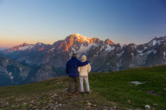 Couple watching sunrise over Mont Blanc summit Royalty Free Stock Images