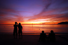 Couple watching sunset. Scenery of couple watching sunset by the beach Stock Image