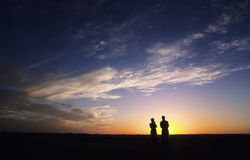 Couple watching the sunset. Sahara desert, Algeria, Africa Stock Images