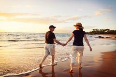 Couple Watching Sunset at the Beach. Senior Couple Enjoying Sunset at the Beach stock image