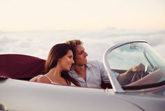 Couple Watching the Sunset in Classic Vintage Car Stock Images