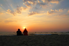 Couple watching the sunset. Indian couple sitting on the sand and watching the sunset in Goa Stock Photography