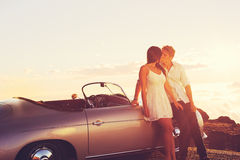 Couple Watching the Sunset and Kissing with Classic Vintage Car Stock Images
