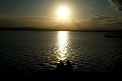 Couple watching the sunset in the lake. Couple watching a sunset in the lake Stock Photos