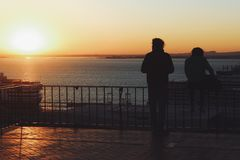 Couple watching sunset in Lisbon stock image