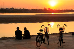 Couple watching sunset at Mekong river. Silhouetted couple watching sunset at Mekong river waterfront, Vientiane, Laos, Southeast Asia Stock Photo