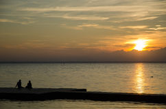 Couple watching sunset at a pier. Silhouettes of a couple watching sunset at a pier Royalty Free Stock Images