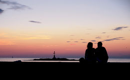 Couple watching the sunset by the sea. In Porec, Croatia Royalty Free Stock Photos
