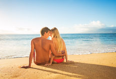 Couple Watching the Sunset on Tropical Beach Vacation. Happy Romantic Couple Watching the Sunset on Tropical Beach Vacation Stock Image