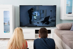 Couple Watching Suspense Movie On Television Royalty Free Stock Images