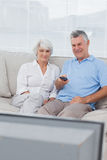 Couple watching television on the couch Stock Images