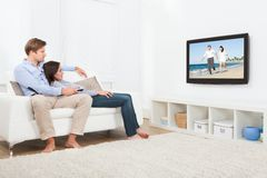Couple watching television at home. Full length of relaxed couple on sofa watching television at home Stock Photos