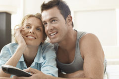 Couple Watching Television At Home. Happy young couple watching television at home Royalty Free Stock Photo