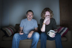 Couple watching television laughing and embarrassed Royalty Free Stock Photos
