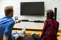 Couple watching television sitting comfortably on floor Royalty Free Stock Images