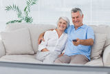 Couple watching television sitting on the couch Stock Photos