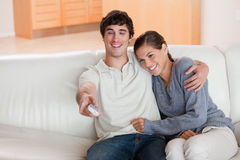 Couple watching television on the sofa Stock Photos
