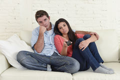 Couple watching television together at home sofa couch looking bored frustrated switching channels Royalty Free Stock Photo