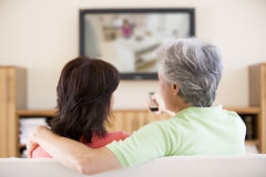 Couple watching television using remote control Stock Photos