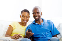 Couple watching TV. Happy african american couple watching TV on sofa Royalty Free Stock Photos