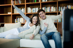 Couple Watching TV. Young couple celebrating while watching TV Royalty Free Stock Photography