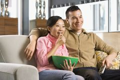 Couple watching TV. Asian couple watching television together royalty free stock photo