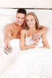 Couple watching TV in bedroom. Young happy couple watching TV whilem lying in a bed Royalty Free Stock Image