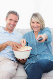 Couple watching tv and eating popcorn on the sofa Royalty Free Stock Images