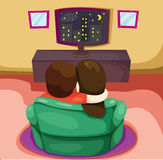 A couple watching TV on a green chair Stock Photo