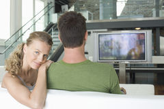Couple Watching TV At Home. Portrait of happy young women with men watching TV at home Stock Images
