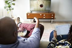 Couple watching TV at home together stock images