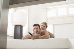 Couple Watching TV At Home. Young couple lying on bed and watching TV at home Stock Image