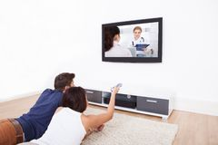Couple watching tv at home. Young couple watching TV while lying on rug at home Stock Images