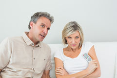Couple watching tv in the living room. Serious couple watching tv in the living room at home Stock Images