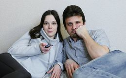 Couple watching TV lying on the couch. Woman switches channels and watching with interest and man is boring. Couple watching TV lying on the couch. Woman Royalty Free Stock Images
